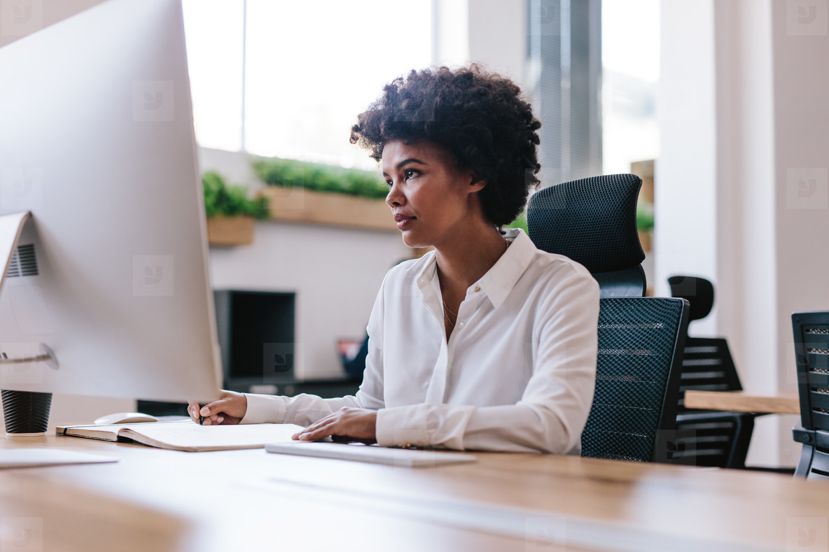 Photos - African woman working at her office desk 154804 - YouWorkForThem